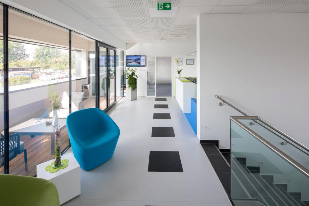 Innenraum des Firmengebäudes der BEROLAN GmbH mit Stiegenaufgang und großen Glasflächen