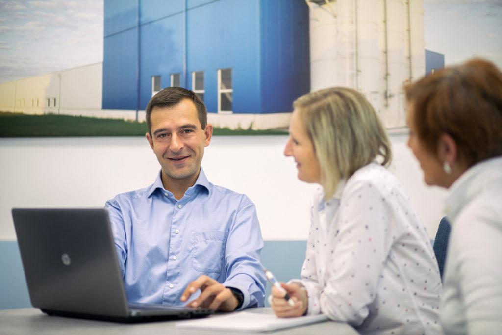 Drei Menschen bei einer Besprechung mit Laptop
