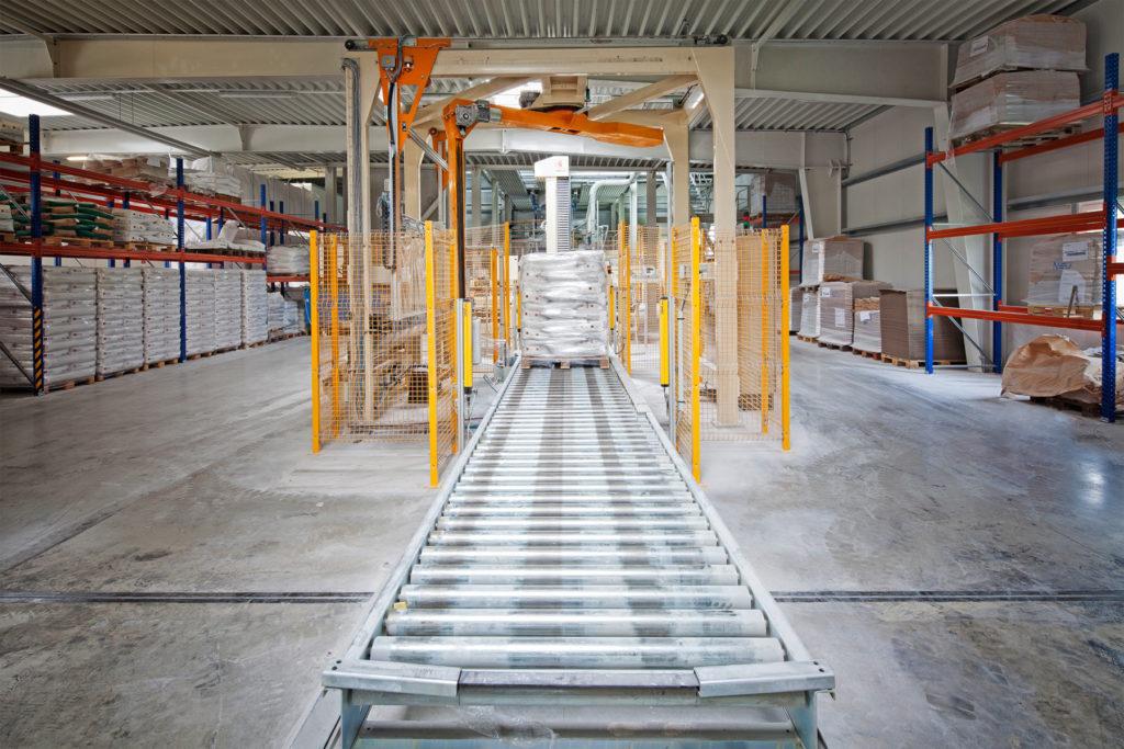 Lager der BEROLAN GmbH mit Fokus auf eine Verpackungsmaschine mit Förderband