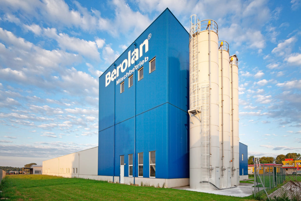 Blaues, hohes  Firmengebäude der BEROLAN GmbH mit drei großen Hochsilos